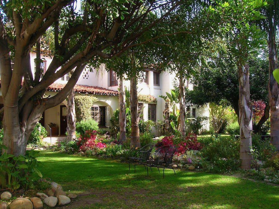 Picture of a two story house with flowers and trees in the front yard in Santa Barbara, CA